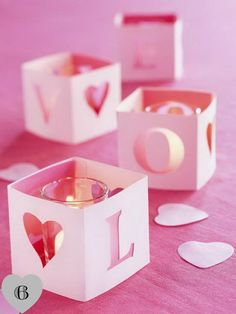 "These are the cutest votive covers! One long strip of paper folded into fours with an extra little tab (to glue the square together). Cut the letters L-O-V-E one on each side and the ""O"" can be a heart for an added touch!"