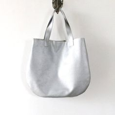 Casual round handbag with its clean round shape and shine metallic vegan leather, my handmade Pitti Vintages spacious silver tote is fail-proof paired with office ensembles and off-duty looks alike. Handmade in Italy. Personalize this bag, choose your favorite color in the variations section for a custom bag!  Label: Pitti Vintage Double handles Magnetic snap closure; lined Interior zip pocket, one interior slip pocket 16L x 14H (41x36cm) 20.5 handle drop (52.5cm) Material: Faux leather…