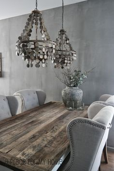 Stunning dining room features silver gray wall color alongside a reclaimed wood dining table lined with gray wingback tufted dining chairs accented with silver nailhead trim illuminated by a pair of gray capiz shell chandeliers. Grey Wall Color, Reclaimed Wood Dining Table, Rustic Table, Reclaimed Furniture, Kitchen Rustic, Plywood Furniture, Rustic Decor, Gray Dining Chairs, Wood Dining Room Tables