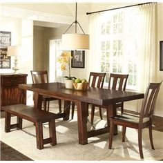Give your dining room a casual spot to enjoy your meals with this welcoming six piece set, featuring a trestle table, four slat back side chairs, and a backless dining bench. The table includes two twelve-inch leaves so that you can extend the surface to suffice for any number of guests.  The trestle legs and iron stretcher support also make this piece a sturdy centerpiece for your dining room.  In addition to this spacious dining table, the charming slat back side chairs feature contoured…