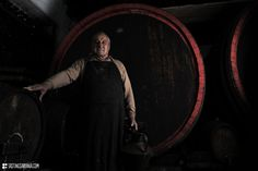 a Vernaccia wine producer in front of a giant barrel in his ancient cellar