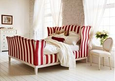 And So To Bed's Churchill is a grand bed with great charisma. Based on a traditional winged armchair, the deep base and soaring head and footboard give you the chance to set your own mood with the upholstery. Choose quiet neutrals for a relaxed setting or go for vivacious colours to raise the energy levels.    Shown here in a contemporary red and white stripe, The Churchill forms a vibrant centrepiece for an all-white bedroom.