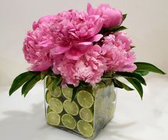 You'll Need: Bunch of bloomed Peonies (at least 5 of 6 blooms), 8-10 large limes, 6-inch square glass vase, 5-inch square glass vase and Wet floral foam.  Instructions: Place 5 inch vase inside 6 inch vase. Slice lemons thin and layer the slices in between vases. Place wet floral foam inside floral foam. Stick stems of Peonies into floral foam. Fill 5-inch vase with water.