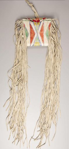 "A PLATEAU PARFLECHE CASE, c.1890 painted on the front with geometric forms in yellow, red, green and outline blue, trimmed with long hide fringe. Parfleche designs and color concepts had a direct influence upon Crow beadwork. For further discussion, see Lanford, Benson, ""Parfleche and Crow Beadwork Designs"" in American Indian Art Magazine, Winter, 1980, vol. 6, no. 1. Lee and Lois Minor, Yakima, WA. Length: 40 inches. Heritage Auctions. 2007 Dallas, TX - American Indian Art Signature…"