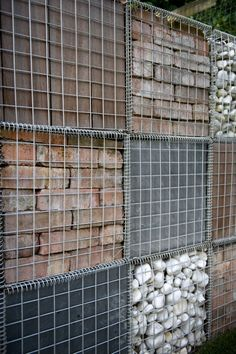 . A wire gabion wall, filled with a selection of red brick, slate tiles, logs (ideally from the felled Sorbus), and wine bottles, will form the backdrop to the garden. This decorative wall will serve to mask a bike store from the main garden.#wire #gabion #gardenwall #bricks #pebbles