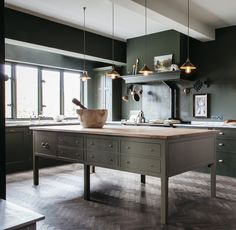 "Love this ""island"" which is more of a baker's table with good storage.  Also like the simple range hood detail"