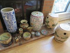 """14 pieces of Asian porcelain and cloisonné including planters with painted koi inside, vases, small jars, pair of ceramic garden stools ecru with floral motif 16""""T, white 18"""" tall brightly colored vase, small stacking cloisonné boxes, blue and white 17"""" umbrella stand, cloisonné covered dish."""