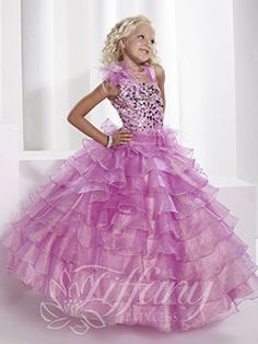 So posh, large circle sequins adorn the bodice of this darling Tiffany Princess 13340 Flower Girl dress. This pageant worthy look has an asymmetrical cut bodice with a diagonal neckline and flower detail on one shoulder topping chic satin straps. A pleated band sits at the natural waistline. The ball gown skirt is made of ruffled tiers of shimmer organza for that full silhouette of her dreams. This hot little number is available in Rose, Pink, and Aqua Blue.