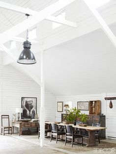 Dining space in a bright white barn with oversized light pendant.