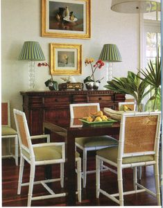 A brown Parsons-style table contrasts with caned bamboo chairs that don bright white-painted frames. Dining Room Table, Dining Area, Dining Chairs, Dining Rooms, British Colonial Style, Brown Furniture, Wood Furniture, Tropical Decor, Traditional House