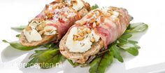 Smakelijk+voorgerecht+of+hapje+van+stokbrood+met+geitenkaas+en+pijnboompitten+omwikkeld+met+spek