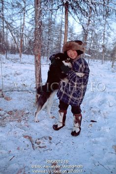 Image of misha elrika, an even boy, plays with a dog at a reindeer herders' camp in northern evensk. magadan region, russia by ArcticPhoto