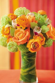 Orange ranunculus and roses mixed with green viburnum and cymbidium orchids. Inside the clear glass vase, ginger leaf