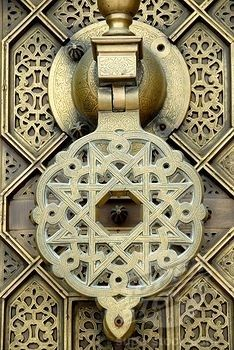 Looks like a brass door knocker to me, but I love the intricate patterns.