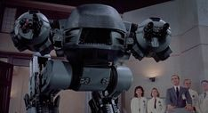 RoboCop (1987) - The Enforcement Droid series 209, or simply, ED-209, is armed with numerous heavy weapons. Referred as having a 'modular weapons system', the left 'gun-arm' contains two 20mm cannons while the right contains a single 20mm gun and three missile launchers (firing heat-seeking missiles). The ED-209 unit also contained twin launchers in a pocket behind the head that could fire either explosive mortar rounds or gas grenades