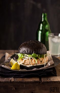salmon burger on a black brioche bun with crunchy greens. They are excellent at @flaxandkale !!