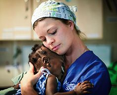 Mercy Ships volunteer embraces a young child receiving surgery