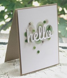 "Starburst stamps in shades of green are all the color you need on this handmade hello card. The word ""hello"" has been cut twice for additional thickness. Green sequins and tiny wooden stars complete this white and kraft card."