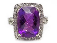 This shimmering ring features a 14x10 mm (4.75 ct) checkerboard, cushion cut, genuine amethyst surrounded by a halo of .25 ctw of genuine, round diamonds. The look is big and fabulous! The setting is solid 14k white gold. #AmethystDiamondRing #AmethystHaloRing
