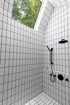 This bathroom has white tiles, but they have used black grout to match the…