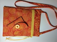 Handmade crossbody bag and wallet of cotton fabric and cotton batting. Large open pocket on back and zippered closure on front. Zipper pull is satin ribbon. 7 x 9 inches with 52 in strap on bag. Wallet is made of same fabrics and has three card pockets as well as a coin pocket with Velcro closure. When closed it measure 4.25 x 3.25 inches and open is 4.25 x 8.5 inches. Tri-folds with Velcro closure.