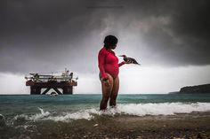 Photo by @jasperdoest // DVM Odette Doest (@vetdoest) stands in the pouring rain holding her brown booby 'Piper' after their weekly swim together in the Caribbean sea.  The bird was found on the rocky shore by Sea Aquarium manager Chris Richards, who took it too Doest's veterinary practice in Julianadorp. Wildlife rehabilitation is a process that involves safely capturing, examining, diagnosing, and treating the animals using proper veterinary and hospital care, feeding, physical therapy…