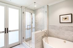 Beautiful bathroom features upper walls painted light gray, Benjamin Moore Moonshine, and lower walls clad in gray marble framing IOS Bathtub by Victoria and Albert paired with a vintage style tub filler beside a walk-in shower clad in grey marble surround.