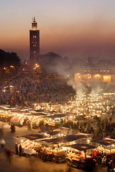 Morocco, Marrakesh, illuminated Djemaa el Fna square at night, Koutoubia Mosque in background