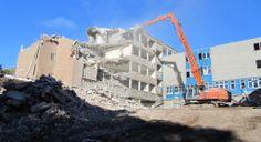 1. High-reach machine demolishing the 1960s building