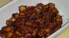 Tofu cubes are marinated in soy sauce, maple syrup, ketchup, vinegar, and seasonings, and then baked in the oven. The tofu can be used as a hot or cold snack or as a salad topping.