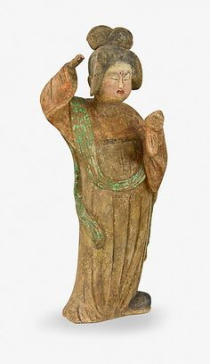 A lady in formal dress examining her hair in a mirror -- a painted pottery figure, Tang Dynasty (618-907)