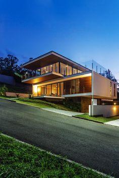 Galeria da Arquitetura | Casa LB - No terreno em aclive, a estrutura em balanço, a planta invertida e os fechamentos envidraçados absorvem a exuberante natureza da baía de Cacupé, em Florianópolis                                                                                                                                                     Mais