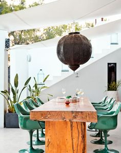 Statement furniture, like this stunning reclaimed wood table, teal designer chairs and an oversized Moorish pendant adds a real wow factor to this garden area.