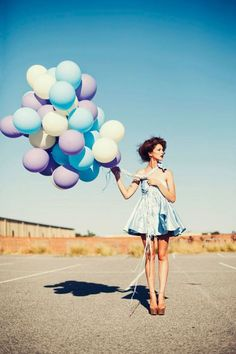 Stylish black & white fashion photography, outdoors with a bunch of balloons;