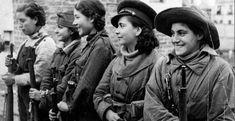 Un grupo de jóvenes mujeres forman sosteniendo unos fusiles.- MUJERES EN GUERRA