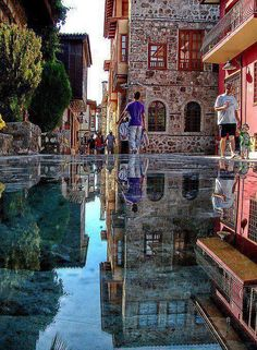 Old City (Kaleiçi) of Antalya. In front of Alp Paşa Hotel. They put glass protection over the ancient stones found in that street. And most probably there is some water over it that it is reflecting that much.It was posted as a correction to a title of the photo on another site: