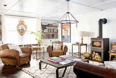 The owners of this Pennsylvania home removed the cabinet doors underneath the window seats in their living room to create a clever spot to stash logs for the woodstove.  Bright idea: When it comes to hanging wall art, don't overlook the mullion bar between two windows.   - CountryLiving.com