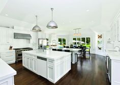 A Hamptons kitchen. - we love the double islands and dining table, along with the black and white contrast!