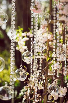 Gorgeous pink blooms, hanging crystals and glass spheres filled with votives are suspended from an enchanted arbor.