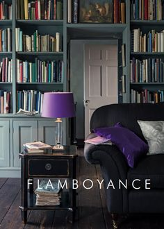 Dark stained wooden floors, grey wall-to-wall book shelves, charcoal sofa, black distressed side table, all lit up by the purple table lamp and cushion. Spring Summer 2014 Laura Ashley, Flamboyance.