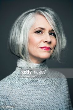 Mature woman with silvery, grey hair in front of a dark grey background wearing red lipstick with a soft smile, portrait.