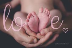 Newborn studio photography pose with parent spelling the word love with feet idea