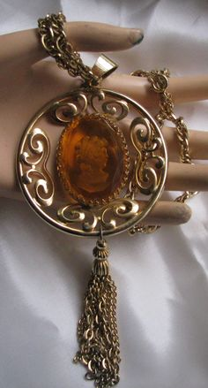 Gold tone necklace with large amber coloured stone with cameo carving on back http://vintagecollector.ca/