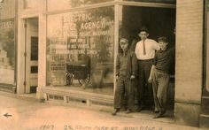 """A man and two boys stand in the doorway of the Electric Package Agency, at 22 South Park Street in Mansfield Ohio (circa A sign painted on the window says, """"baggage, package, freight received from and forwarded to all points on suburban electric lines. Mansfield Ohio, Local History, Junk Drawer, South Park, Painted Signs, Doorway, Baggage, Electric, Window"""