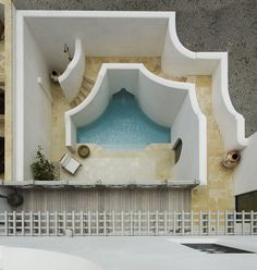 """The family's 50-foot-square plot being so small, Imber didn't """"want the pool to feel as though it was crammed into leftover space."""" An electrical transformer also took a chunk out of the site, though the resulting shape reminded him of a seashell. His design expands the pool's reach by """"pushing it under the stair, and wrapping the stair up, over, and around it."""" A courtyard also delivers the blessing, Imber explains, of light and views for adjoining interiors, to apparently expand them."""