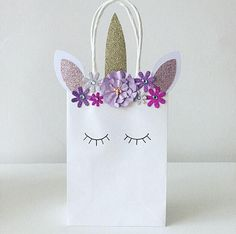 Magical handmade party bags - the perfect finishing touch to any unicorn themed party. ▫️Handmade with love ▫️Unicorn theme ▫️Unicorn head design ▫️Embellished design ▫️White paper bag 12cm x 18cm x 6cm ▫️Other sizes also available ▫️Matching invitations available ▫️Production time is approximately 3-5 days - Please contact me if you need a rush order BESPOKE DESIGN SERVICE AVAILABLE. PLEASE CONTACT ME FOR OTHER CHARACTERS/ THEMES. DISCLAIMER: This item is not a licensed product. You ar...