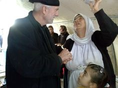Pastor William Devlin listens to a Yazidi woman at a refuge camp in Dohuk, Iraq, in this undated photo.