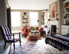 """Bold Color and Pattern  Stylist Peter Frank's 30-foot-long master bedroom in his Hudson Valley home was originally two rooms. """"It's long and narrow, so I kept adding color and pattern until it felt comfortable,"""" he says. """"The mix is more exuberant than the rest of the house."""" Orange chesterfield sofa is vintage. Walls are Benjamin Moore's Victorian Garden."""