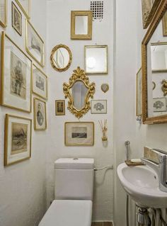 bathroom picture walls - narrow white European bath with gilded frame pictures and mirrors - keltainentalorannalla.blogspot.fr via attticmag