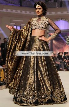 BW6952 Black Crinkle Chiffon Banarasi Jamawar Lehenga This extremely feminine lehenga wear is traditional yet trendy.. . Top: Black Crinkle Chiffon Short length blouse features sweet and lovely embellishments accentuates all over the front and sleeves cuffs. Full length sheer sleeves. High neckline. Concealed hooks closure back. Dangling beaded balls on hemline. Lining inside. Edges finished. Bottom: Black Banarasi Jamawar Comes with beautiful lehenga skirt adorned exquisite embellishments a